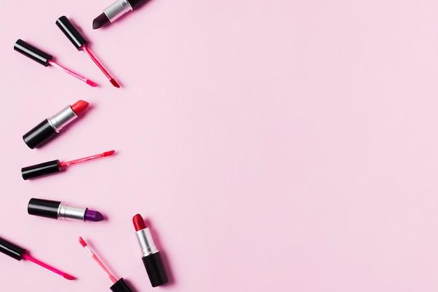 Помады и блески для губ, разбросанные на розовом фоне Бесплатные Фотографии