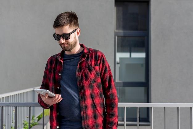 Взрослый мужчина используя таблетку снаружи в городе Бесплатные Фотографии
