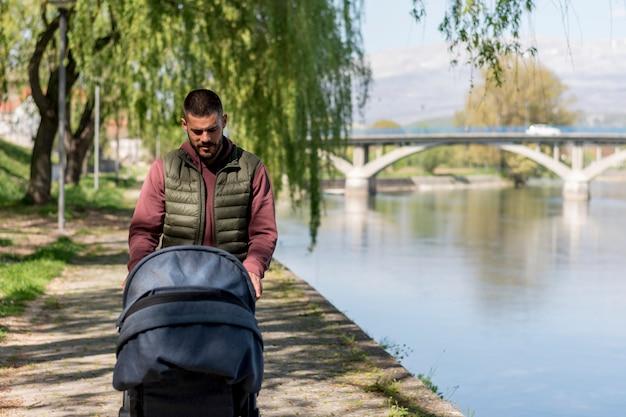 川の近くのベビーカーと一緒に歩いている成人男性 無料写真