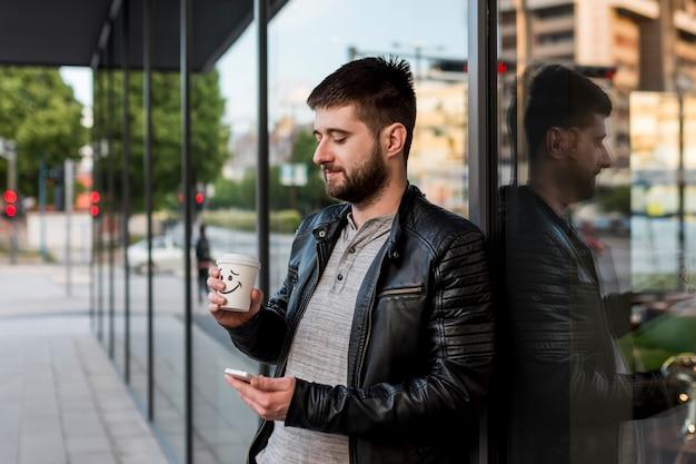 コーヒーとスマートフォンの外に立っている成人男性 無料写真