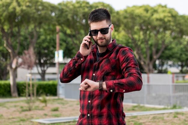 耳の近くのスマートフォンを押しながら時計を見てサングラスをかけた男性 無料写真