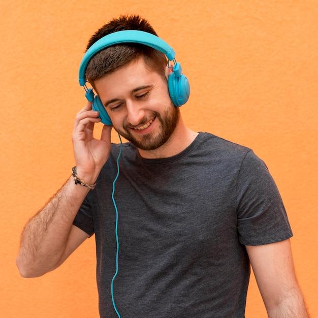 ハンサムな男性がヘッドフォンで音楽を聴く 無料写真