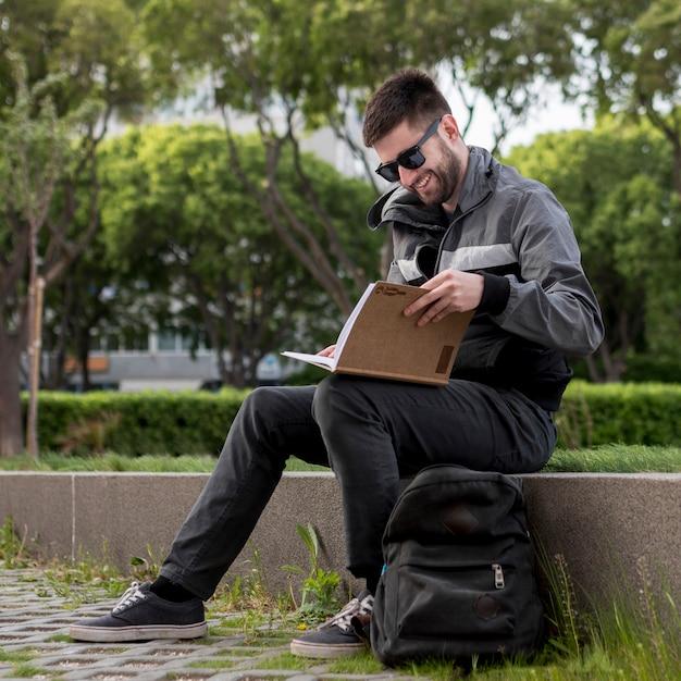 Улыбающийся человек читает книгу на улице Бесплатные Фотографии