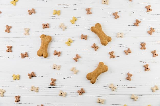 Композиция с лакомствами для собак на белой поверхности Бесплатные Фотографии