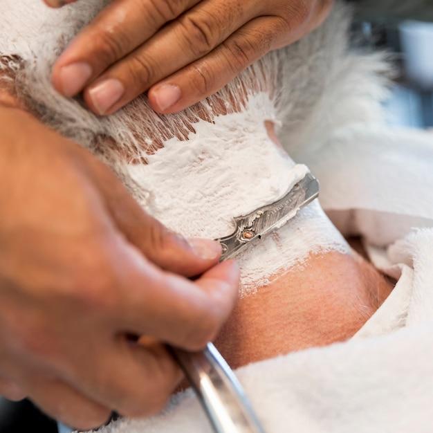 ストレートかみそりで男性の首を剃る 無料写真