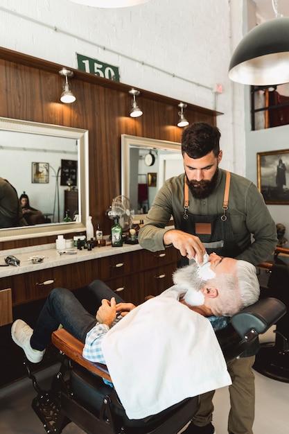 美容室の老人にシェービングクリームを適用する理髪師 無料写真