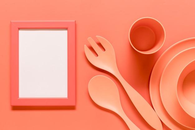 Розовая композиция с пустой рамкой и пластиковой посудой Бесплатные Фотографии