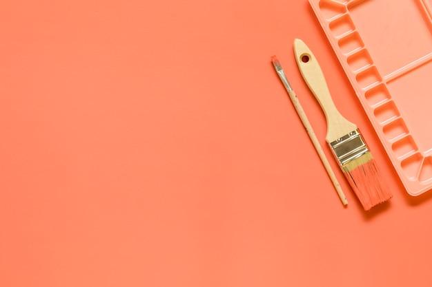 Кисти и палитра на красном фоне Бесплатные Фотографии