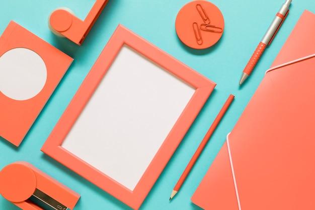 Папка, пустая рамка и открытка возле канцелярских товаров Бесплатные Фотографии