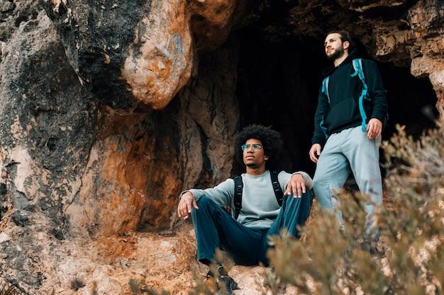 Два мужчины турист возле входа в пещеру Бесплатные Фотографии
