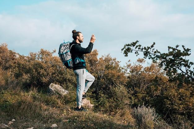 山で写真を撮る彼のバックパックを持つ男性ハイカー 無料写真