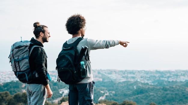 都市の景観上の指を指しているアフリカの若い男を見て男性ハイカー 無料写真