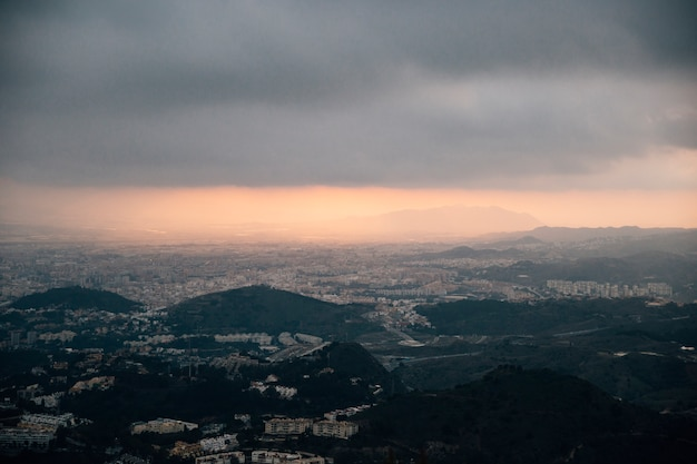 都市の景観と嵐雲の下の山 無料写真