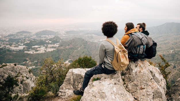 Три женщины и мужчины туристы, сидя на вершине скалы с видом на городской пейзаж и горы Бесплатные Фотографии