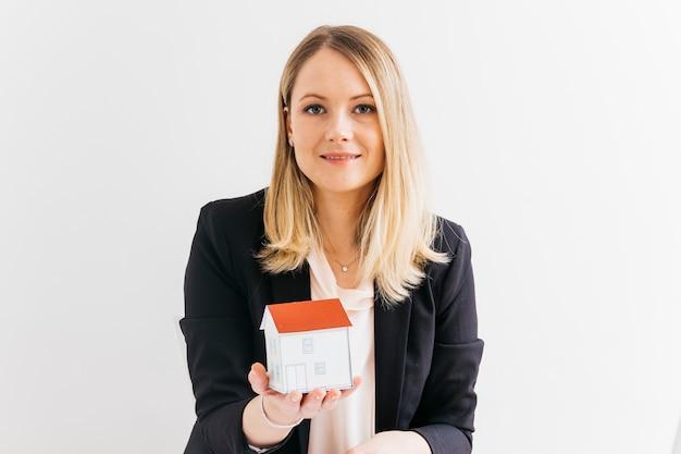 白い背景の上のミニチュアの家モデルを保持している若い実業家 無料写真