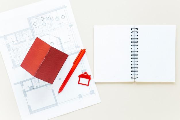 不動産の机の上の青写真と家のモデルの日記を開く 無料写真
