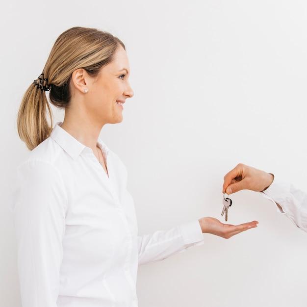 男からキーを受け取る白人女性の笑みを浮かべてください。 無料写真