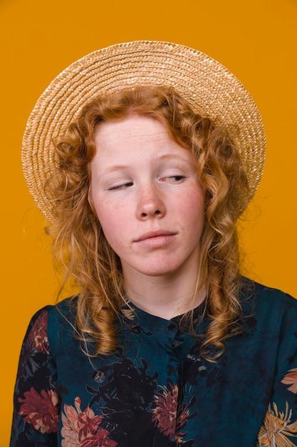 色付きの背景を持つスタジオで興味のある巻き毛の女性 無料写真