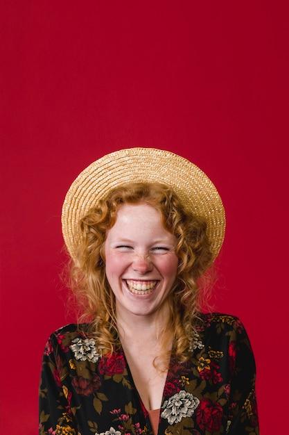 笑って麦わら帽子をかぶっている幸せな若い生姜女 無料写真
