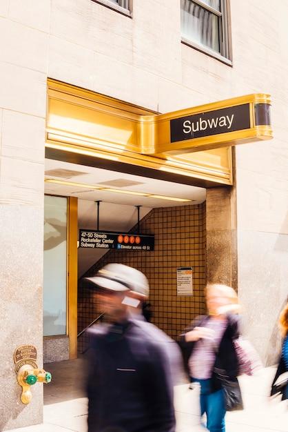 地下鉄の看板の近くを歩く人 無料写真