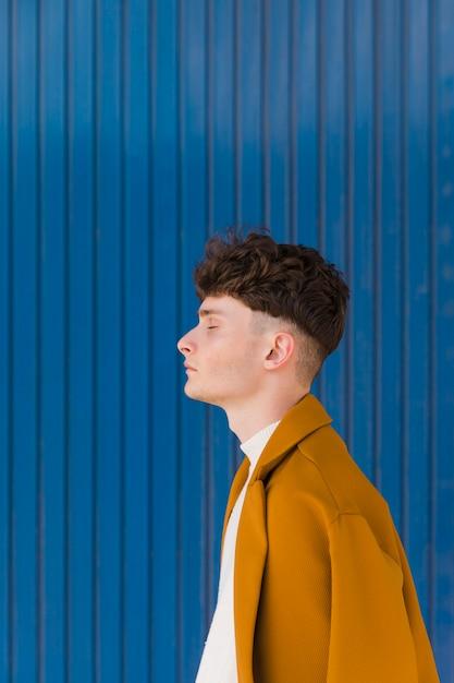 水色の壁に対してファッショナブルな少年の肖像画 無料写真