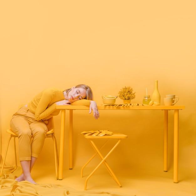 黄色のシーンでテーブルで寝ている女性 無料写真