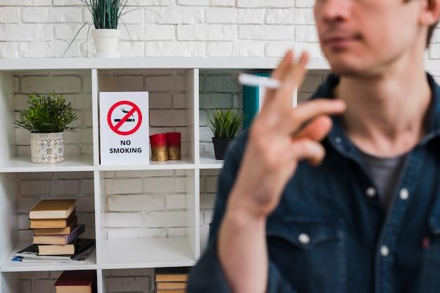 棚の上の禁煙ポスターの前にタバコを持つ男の焦点をぼかします 無料写真