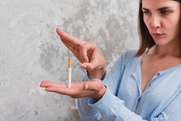 風化した壁に対して彼女の指を通してタバコを投げる女性 無料写真