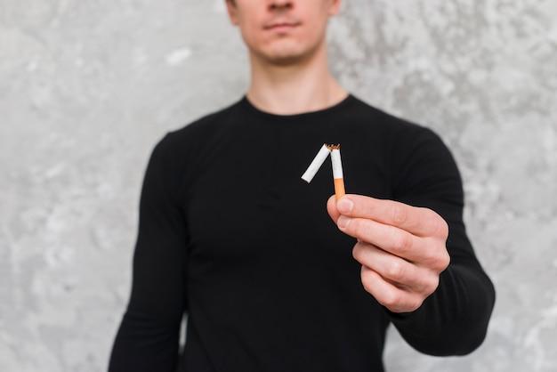Портрет человека, держащего сломанную сигарету Бесплатные Фотографии