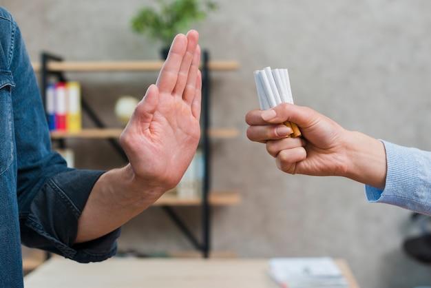 Мужчина отказывается от сигарет, предложенных его подругой Бесплатные Фотографии