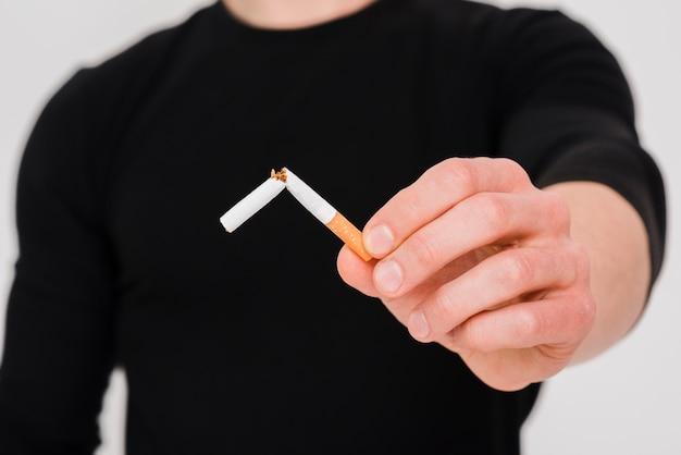 壊れたタバコを示すクローズアップ男の手 無料写真