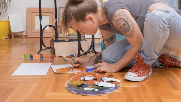 床の上に座ってスタイリッシュな女性アーティスト絵画女性の肖像画 無料写真