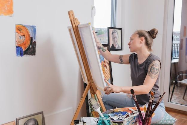 アートスタジオに座っている若い入れ墨女性絵画絵 無料写真