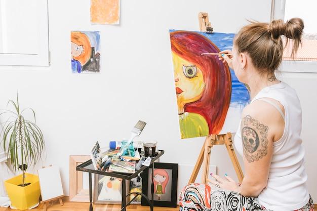 Художник рисует женщину на холсте Бесплатные Фотографии