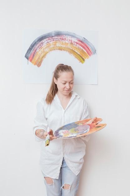 パレットとブラシのワークショップで幸せな女アーティスト 無料写真
