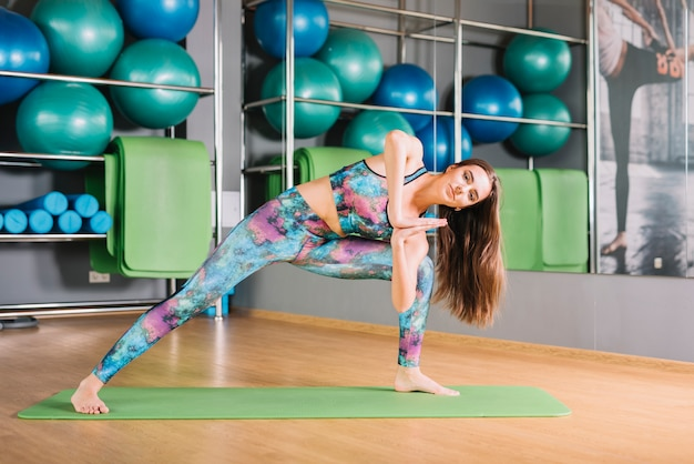 Женщина делает йога позиции в фитнес-центре Бесплатные Фотографии
