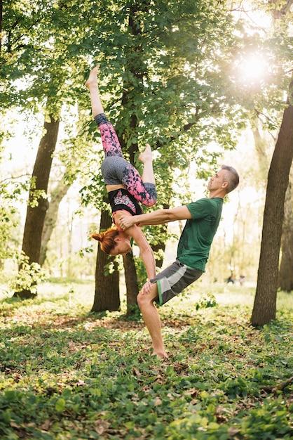 自然の中でアクロヨガのバランスをしている中年のカップルにフィット 無料写真