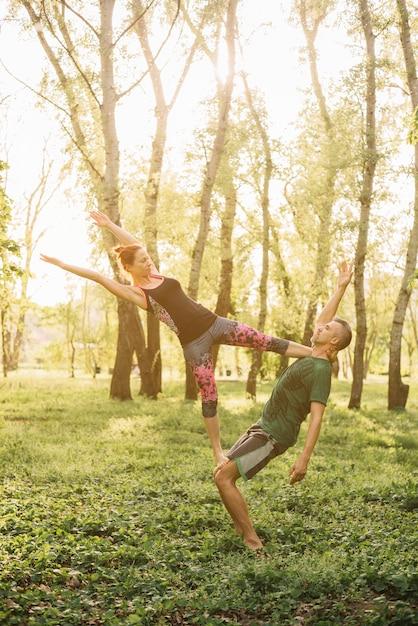 Здоровый мужчина и женщина делают акройога в парке Бесплатные Фотографии