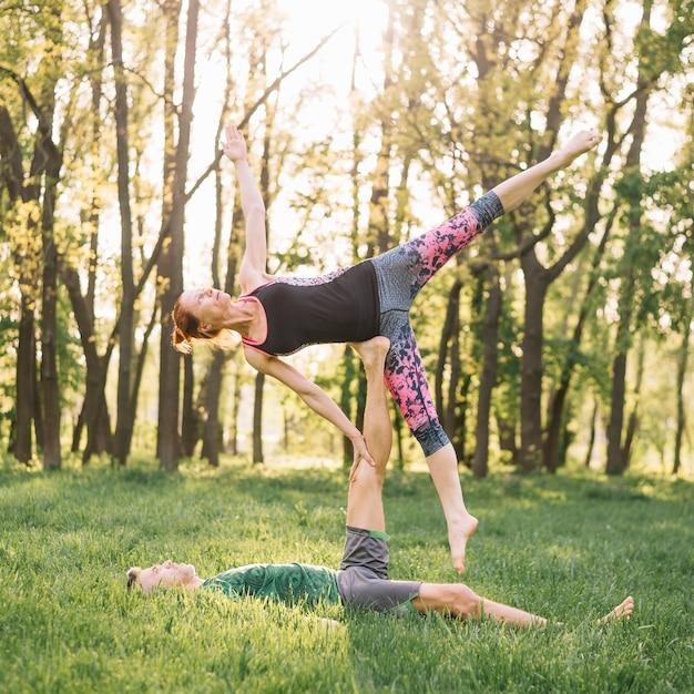 芝生の上のアクロヨガの練習健康な半ば大人カップル 無料写真