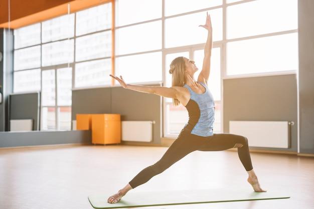 フィットネスジムでトレーニング運動を行う若いヨガ女性 無料写真