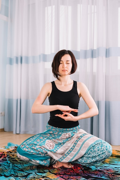 Портрет красивой молодой женщины, сидя в позе йоги Бесплатные Фотографии
