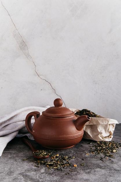 Зеленый травяной заварной чайник с высушенными заварками с салфеткой против стены Бесплатные Фотографии