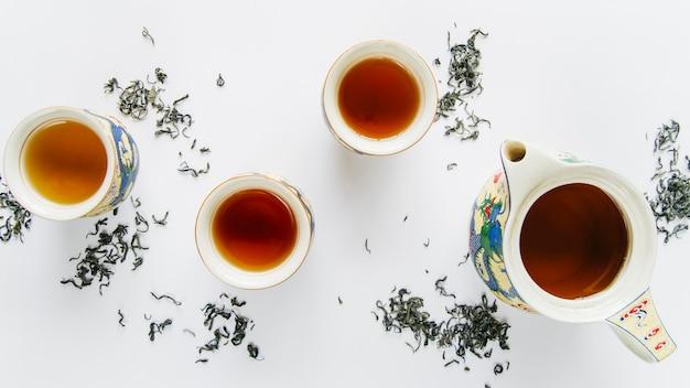 Старинный китайский керамический чайный сервиз с высушенными листьями на белом фоне Бесплатные Фотографии