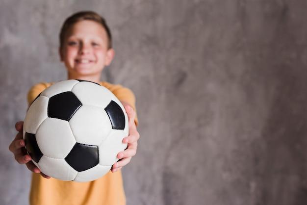 コンクリートの壁のカメラ立っている正面に向かってサッカーボールを示す少年の肖像画 無料写真