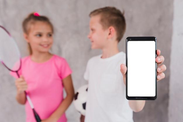 白い画面表示と携帯電話を示す女の子と立っている少年 無料写真
