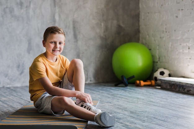 カメラを見て運動マットの上に座って微笑む少年の肖像画 無料写真