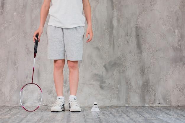 ラケットと羽根で立っている少年の低いセクション 無料写真