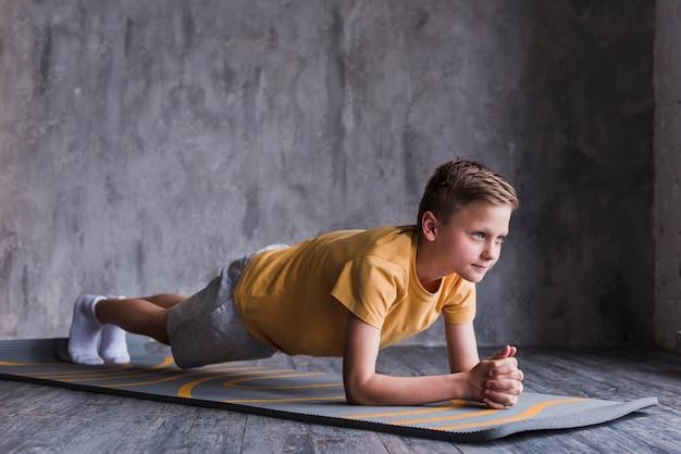 コンクリートの壁の前で運動マットの上を行使の少年 無料写真