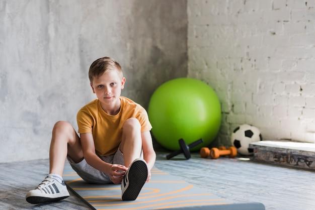 Крупный план мальчика, сидящего на тренировочном мате, связывающего шнурок Бесплатные Фотографии