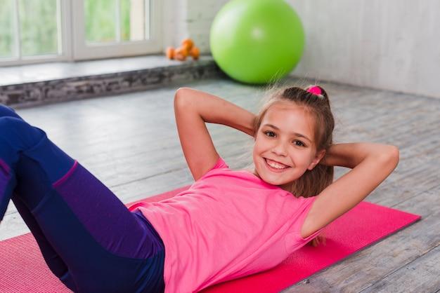 床にストレッチ運動をして背中に横になっている笑顔の女の子 無料写真